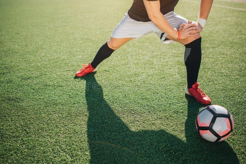 在绿色草坪和舒展腿的足球选手立场 他倾斜到一它 太阳发光外面 说谎除以外的球 库存照片