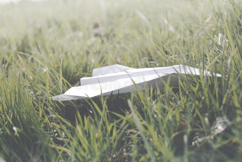 在绿色草坪登陆的纸飞机 库存图片