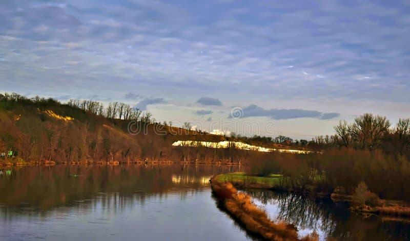 在绿色草甸和池塘之间的一条乡下公路导致小山的一个森林 库存照片