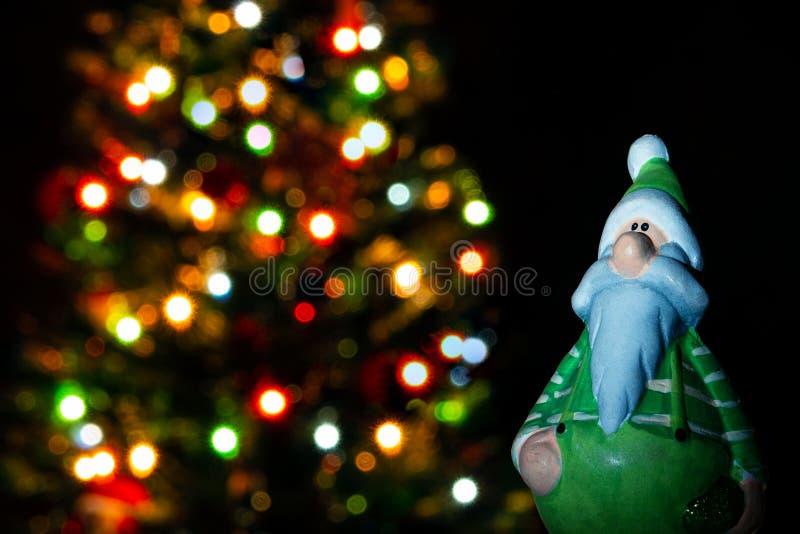在绿色衣裳的圣诞老人项目小雕象在背景与光的圣诞树 免版税库存图片