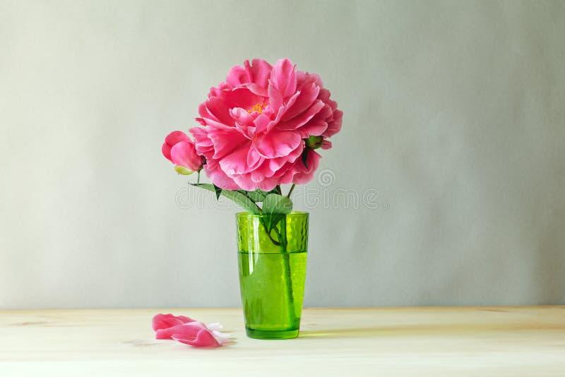 在绿色透明玻璃花瓶的新鲜的桃红色牡丹在木桌上 图库摄影