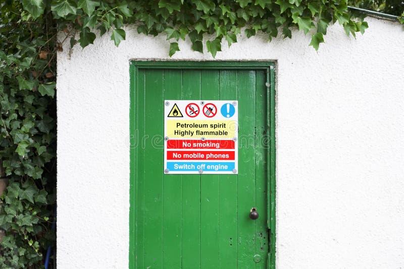 在绿色门的石油液体精神高度易燃的禁烟警告危险标志 图库摄影