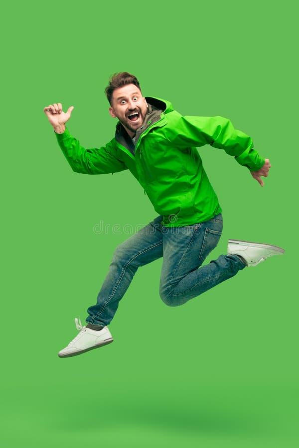 在绿色隔绝的英俊的有胡子的年轻人赛跑 库存照片