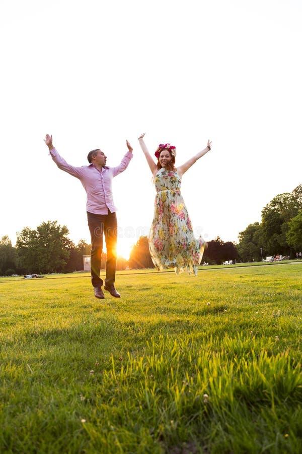在绿色领域的跳跃的愉快的夫妇在夏天公园 免版税库存照片