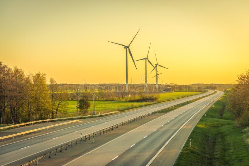 在绿色领域的风力场发电器的图片接近有汽车的路在日落 免版税库存照片