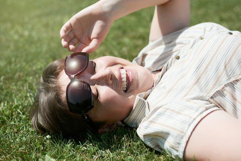 在绿草和半眯着的眼睛从明亮的太阳,室外的夏天的妇女谎言 免版税库存图片