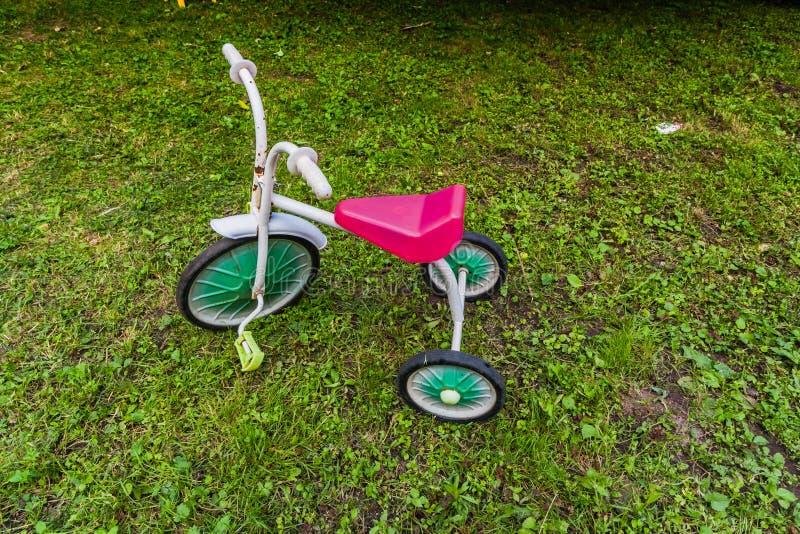 在绿草的儿童三轮车 葡萄酒有红色位子的金属自行车 图库摄影