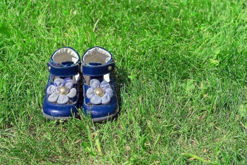 在绿草的儿童的蓝色凉鞋 逗人喜爱的女孩的鞋子在庭院里 童年和夏天的概念 免版税库存图片