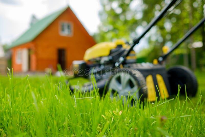 在绿草的割草机和背景的被弄脏的房子 免版税图库摄影