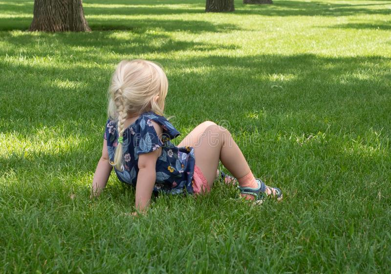 在绿草的女孩开会与膝盖倾向 免版税库存图片