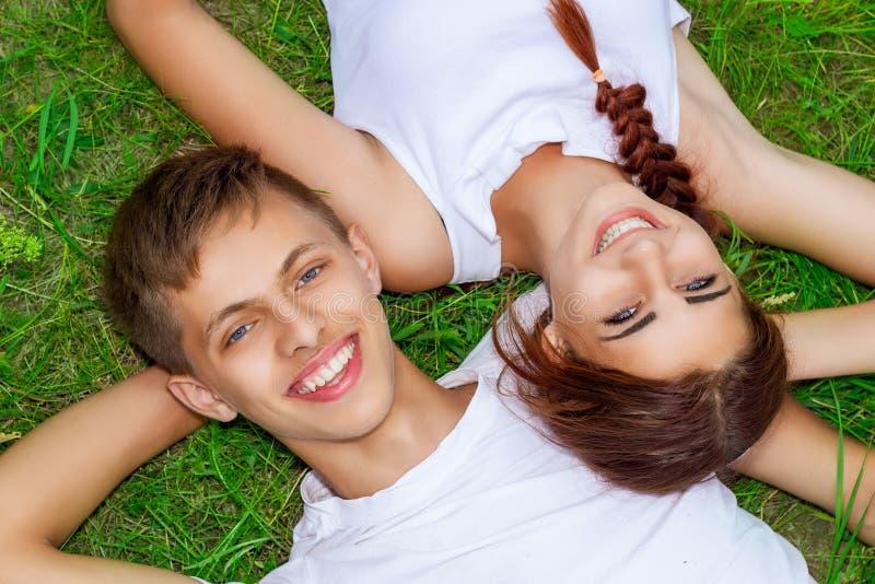 在绿草的美好的年轻夫妇与在面孔的微笑,愉快的关系 免版税图库摄影
