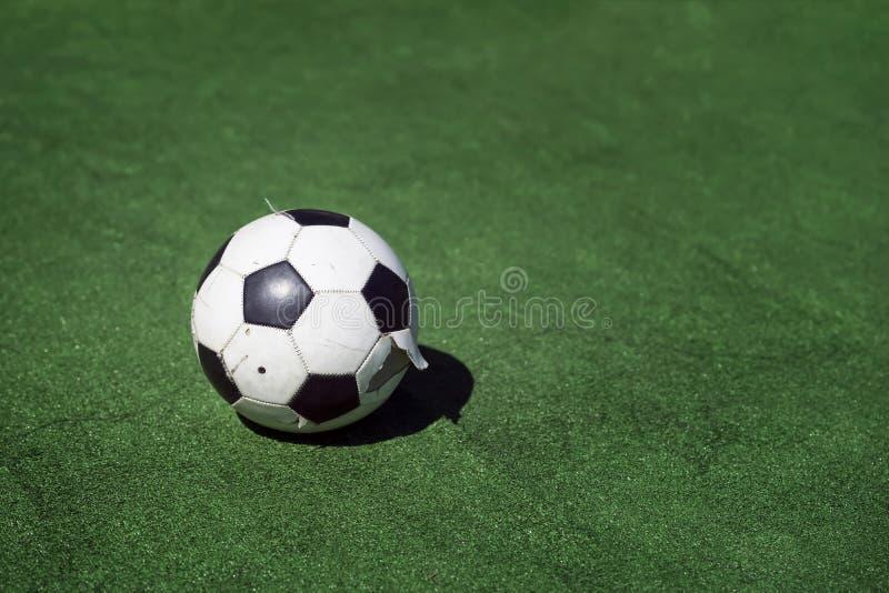 在绿草背景的老,肮脏的被撕碎的足球  在绿色的传统经典黑白橄榄球球 免版税库存图片