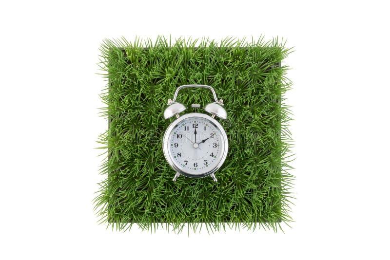 在绿草领域正方形的老牌闹钟在白色隔绝的 免版税库存照片