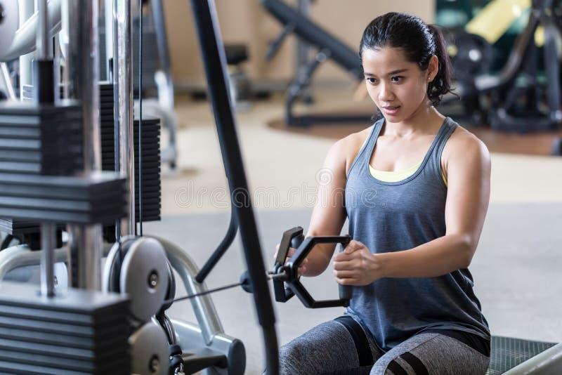 在缆绳机器的强和美好的妇女划船在锻炼期间 免版税库存照片