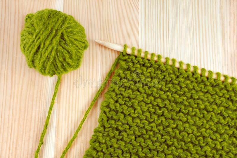 在编织针的绿色羊毛和平针织法 库存照片