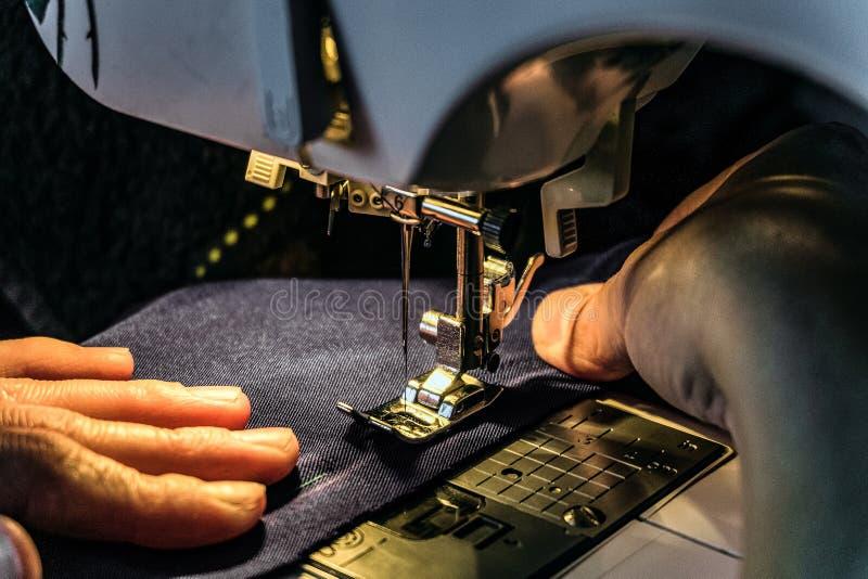 在缝纫机的裁缝工作 由固定硬件灯的光的夜班