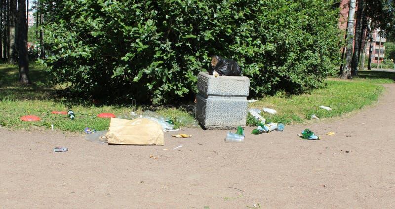 在缸旁边的垃圾在公园,塑料和玻璃瓶,塑料袋 免版税图库摄影