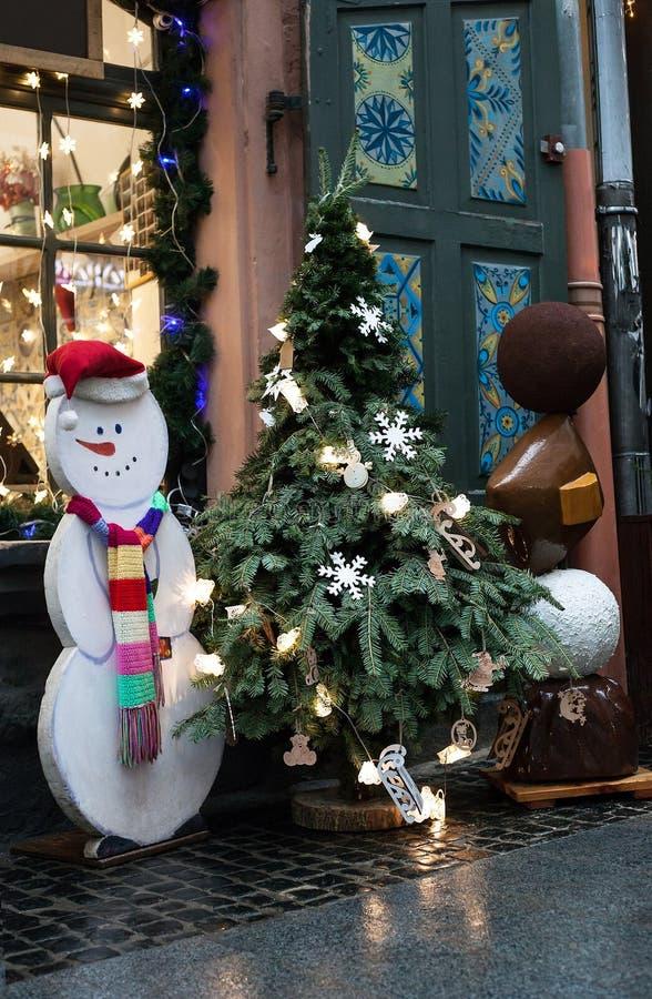 在罐和白色雪人的圣诞树在房子附近 免版税库存图片