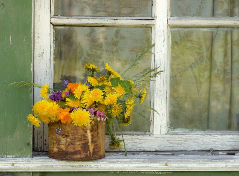 在罐子的花束在老窗口 库存照片
