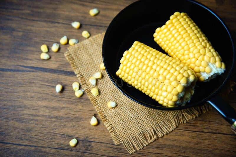 在罐平底锅的玉米烹调的在木背景的甜玉米耳朵 免版税库存图片
