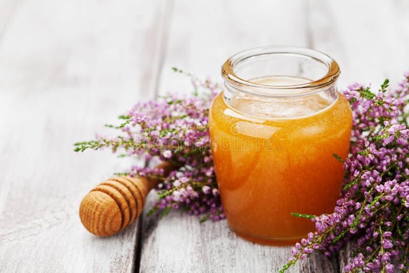 在罐或瓶子和花石南花的可口蜂蜜在木葡萄酒桌上 库存照片
