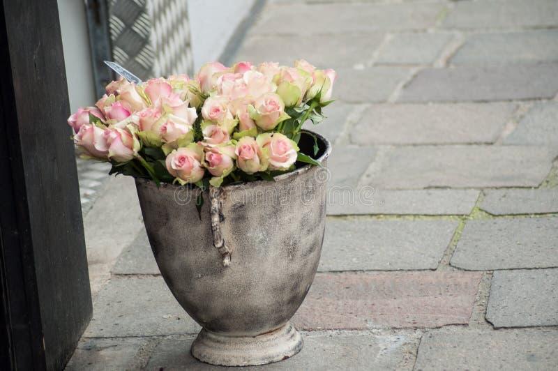 在罐的桃红色玫瑰花束在街道的卖花人 免版税库存图片