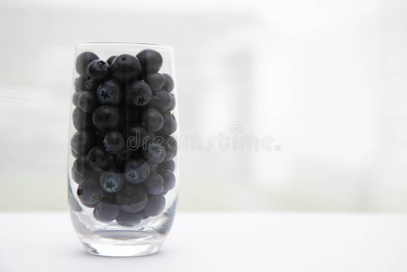 在罐的甜鲜美越桔 与一个玻璃觚的新鲜的蓝莓 在一块玻璃的蓝莓在窗台 白色帷幕 库存图片