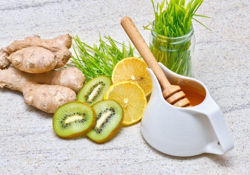 在罐的蜂蜜、绿色麦子、柠檬和姜、猕猴桃新鲜的汁液的或戒毒所圆滑的人 库存照片