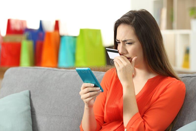 在网上买与信用卡和电话的担心的夫人 库存图片