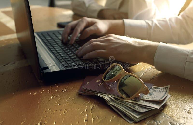 在网上买使用膝上型计算机在一个现代办公室,顶楼样式的愉快的年轻夫妇 库存照片