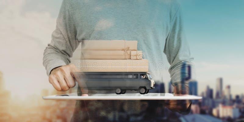 在网上使用数字式片剂购物和送货卡车运载的邮包箱子的一个人 网上购物、电子商务和交付 免版税库存图片