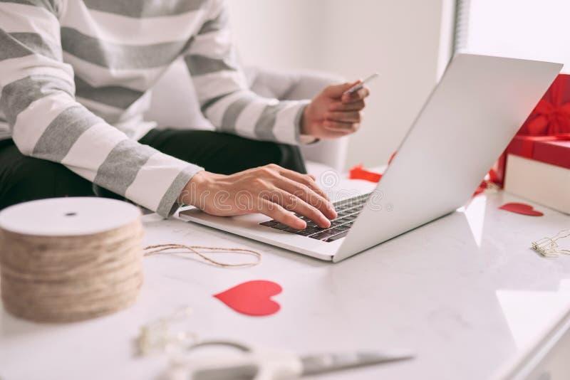 在网上供以人员礼物的购物,当在家时坐长沙发 免版税库存图片