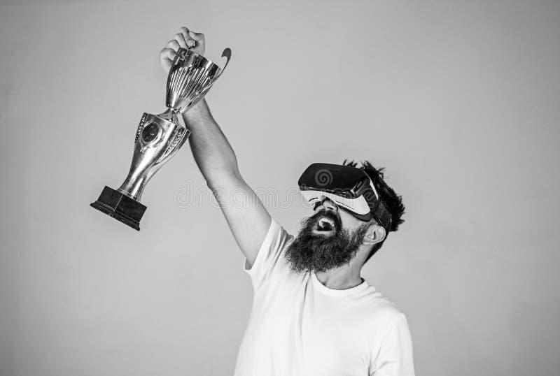 在网上冠军 人有胡子的行家vr耳机拿着金黄觚 在虚拟现实比赛的感受胜利 辅助 免版税图库摄影