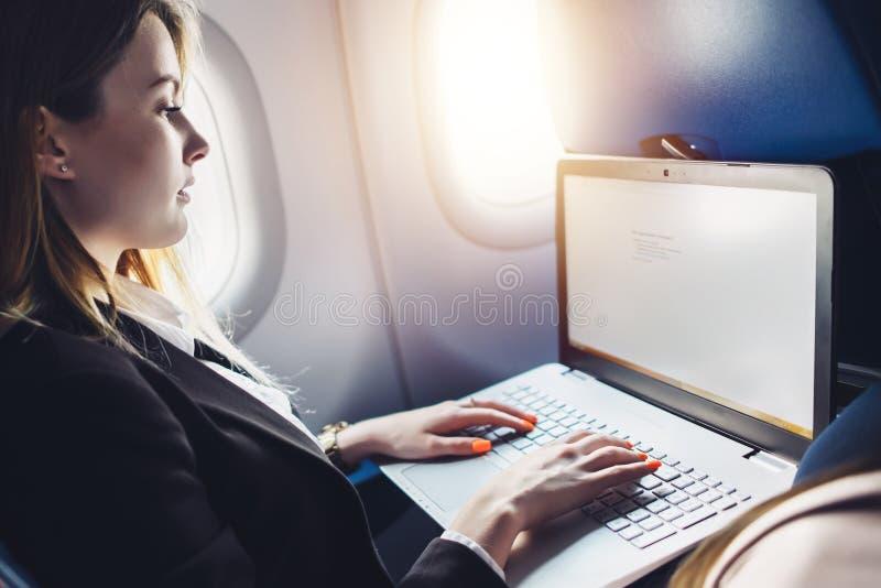 在网上学会通过netbook的年轻女学生,当坐在飞机客舱时 免版税库存图片