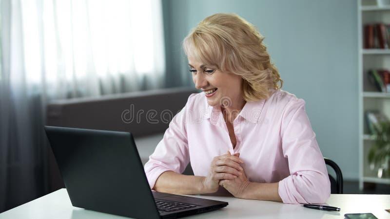 在网上聊天与人的白肤金发的可爱的妇女,日期应用,休闲 免版税库存照片