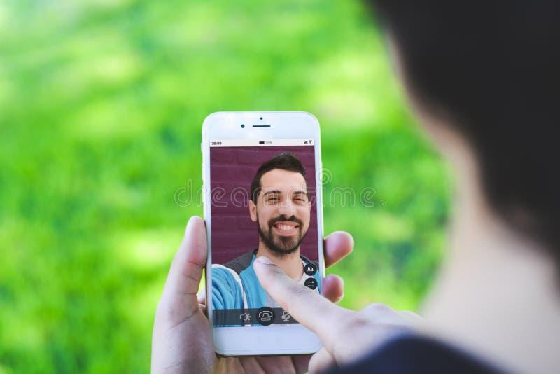 在网上聊天通过打的妇女视频通话在智能手机 免版税库存图片