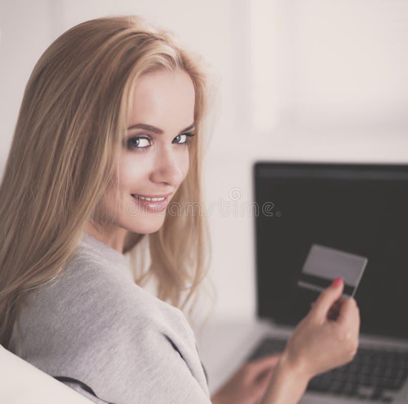 在网上购物与信用卡和计算机的妇女 免版税库存照片