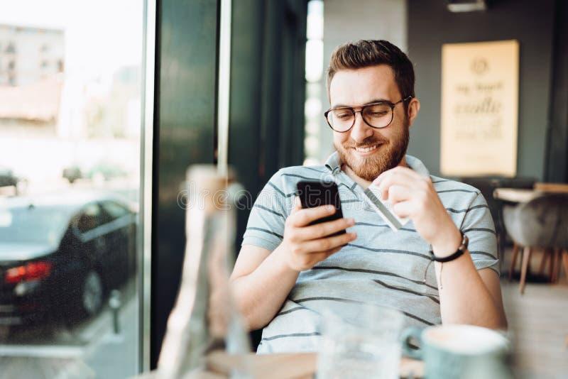 在网上购物与智能手机和支付由信用卡的微笑的人画象 库存图片