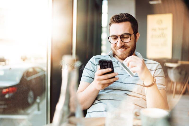 在网上购物与智能手机和支付由信用卡的微笑的人画象 免版税库存照片