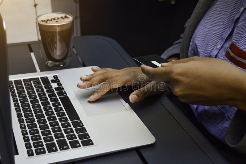 在网上购物使用计算机和拿着信用卡的年轻黑人妇女 网络购物,技术,互联网 库存照片