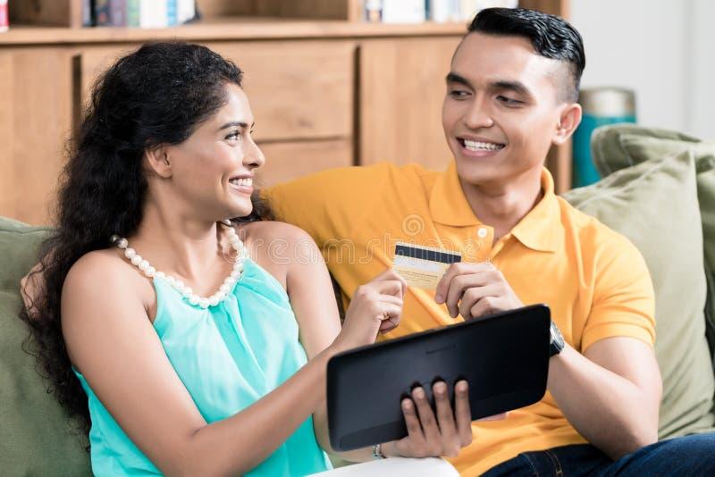 在网上购物愉快的年轻的夫妇 库存图片
