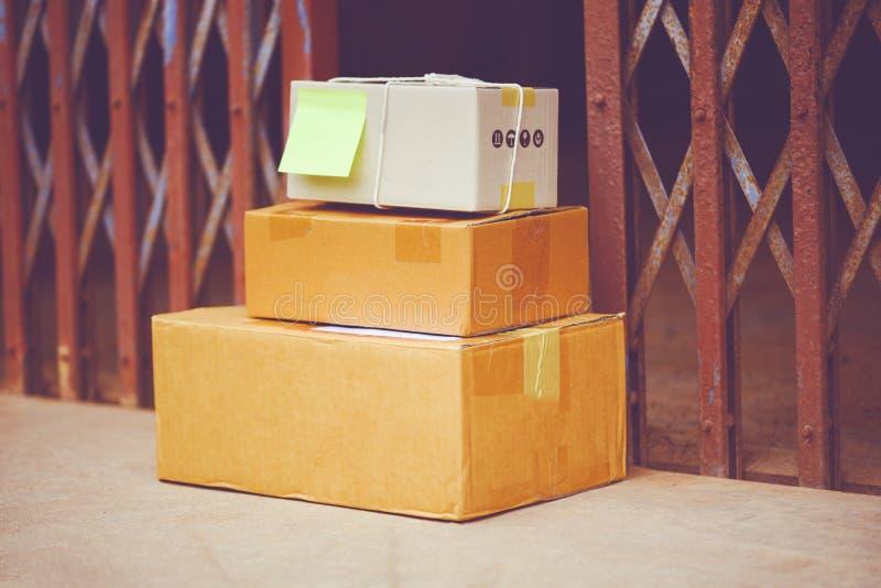 在网上购物电子商务的交付和命令概念-在地板上的被交付的小包在大门钢附近 免版税库存图片