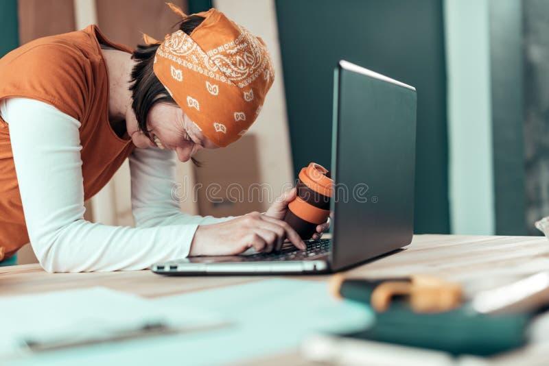 在网上闲谈期间的愉快的微笑的女性木匠 库存图片