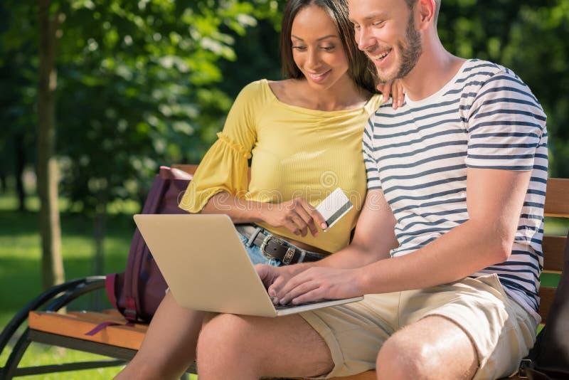 在网上购物与膝上型计算机和信用卡的不同种族的夫妇,当坐长凳在公园时 免版税库存照片