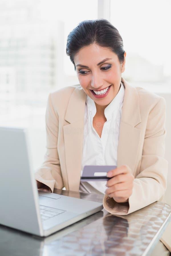 在网上购物与膝上型计算机的快乐的女实业家 免版税库存照片