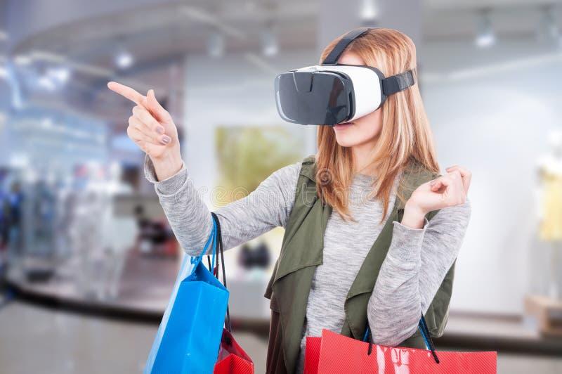 在网上购物由VR耳机的女性顾客 免版税库存图片