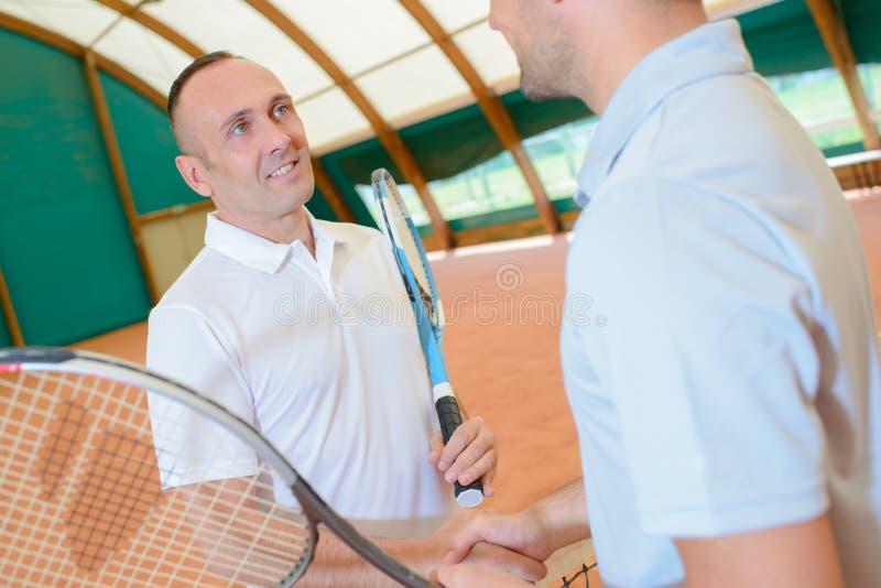 在网球场的手震动 免版税库存照片