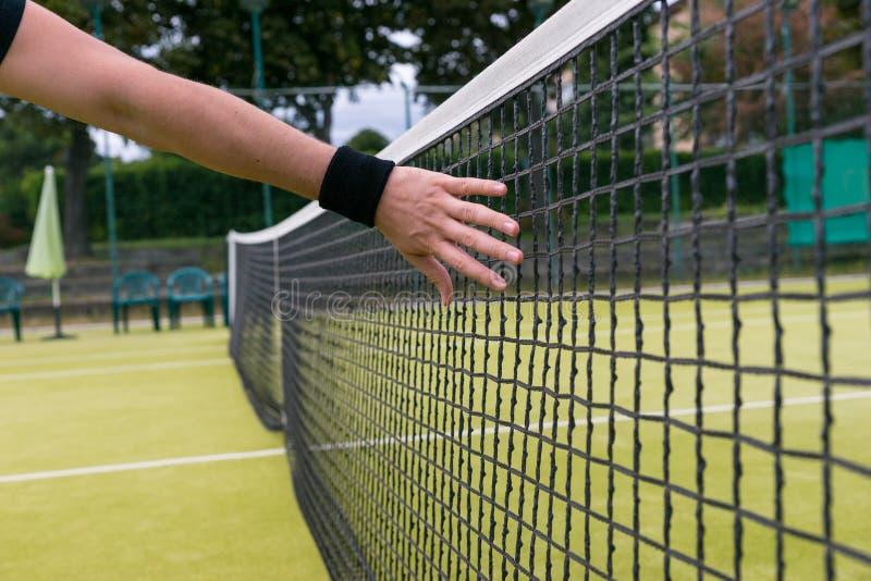 在网球网附近的男性手 图库摄影