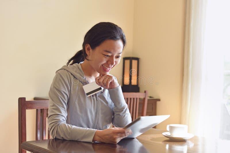 在网络购物期间的愉快的妇女在家 免版税库存图片