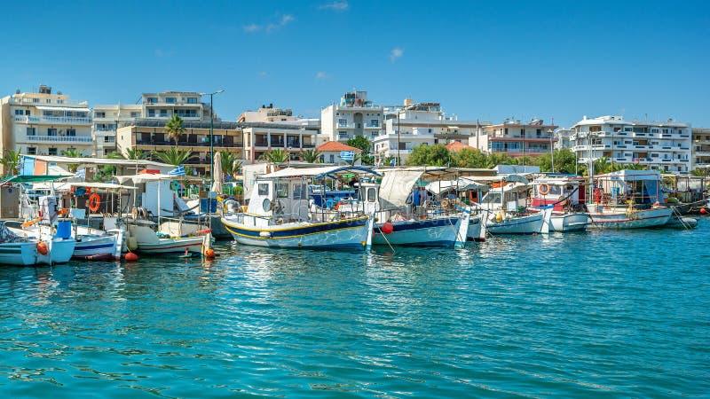 在罗希姆诺,克利特海岛,希腊港的希腊渔船  罗希姆诺港的看法从海边的与小船和 免版税库存图片